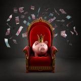 Moneybox-Schwein in der Krone auf dem königlichen Thron Lizenzfreies Stockfoto