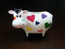 Moneybox som en ko med målade hjärtor Royaltyfria Foton