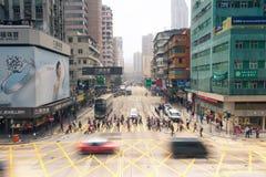 Mong Kok district, Kowloon, Hong Kong. Hong Kong - FEBRUARY 18: People crossing the street at Mong Kok district, Kowloon, Hong Kong on February 18, 2014 royalty free stock image