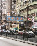 Mong Kok, Hong Kong: Cars, buses, traffic, apartment buildings, signs. Cars and buses travel next to the typical pastel apartment buildings and neon signs of the Royalty Free Stock Photos
