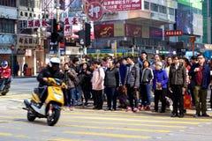 Mong Kok street corner: Motorbike turns, pedestrians wait to cross Royalty Free Stock Photo