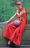 A monge budista na roupa tradicional é descansar exterior fotos de stock