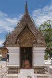 A monge budista reza o ajoelhamento em um santuário dentro do templo de Wat Xieng Thong em Luang Prabang, Laos imagem de stock