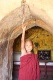 A monge do principiante soa o sino na frente de um templo, Bagan, Myanmar fotos de stock royalty free