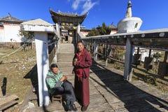 Monge e protetor tibetanos na frente de um templo tibetano em Dragon Jade Snow Mountain em Yunnan, China fotografia de stock royalty free