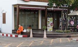 A monge em vestes do açafrão senta-se no pavimento de canto fora do resto asiático Fotos de Stock
