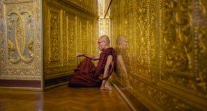 A monge em vestes vermelhas reza no templo do ouro Fotos de Stock