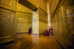 A monge em vestes vermelhas reza o templo interno Imagem de Stock Royalty Free