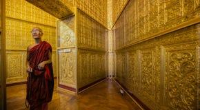 A monge em vestes vermelhas reza o templo interno Fotografia de Stock Royalty Free