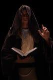 Monge misteriosa que guarda um livro e pregar Fotos de Stock Royalty Free