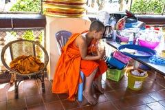 A monge nova escuta a música dentro de Wat Suan Dok Temple, Chiang Mai, Tailândia imagens de stock royalty free
