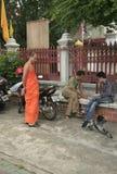 Monge que olha o jogo do seu amigo perto de seu templo Foto de Stock