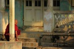 A monge sentou-se enfrentando a construção velha fotos de stock royalty free