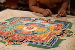 Monge tibetana solitária que trabalha na mandala Foto de Stock