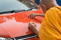 A monge unta o pó santamente em um carro novo fotografia de stock royalty free