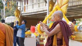 A monge usa o telefone celular com um écran sensível no templo da Buda dourada tailândia vídeos de arquivo