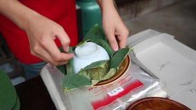 Monger toont methode die rijst maken die door lotusbloemblad wordt verpakt in suan 100 jaarmarkt van Klong stock video