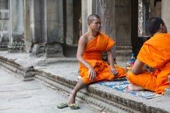 Monges cambojanas que sentam-se em escadas no templo de Angkor Wat, Camboja Foto de Stock Royalty Free