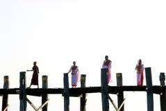 Monges que cruzam a ponte do bein de u, amarapura, myanmar Imagem de Stock