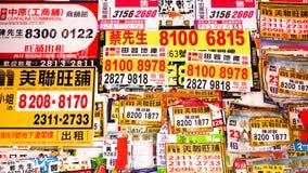 Mongkok/Hong Kong - DICIEMBRE DE 2016: Anuncios y carteles de agentes inmobiliarios y de promotores de propiedad fuera de una ofi imagen de archivo