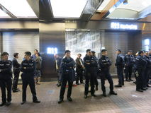 Mongkok Police Officers Standing on Street. HONG KONG, DEC. 6, 2014: A group of police officers stand outside a closed jewelry store in Mongkok at night to stock photos