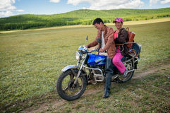 Mongol traveling with his wife on a motorcycle Royalty Free Stock Images