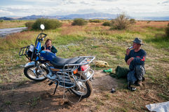 Mongol traveling with his wife on a motorcycle Stock Photo