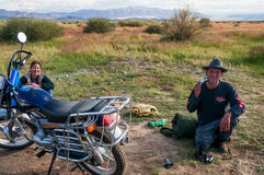 Mongol traveling with his wife on a motorcycle Royalty Free Stock Photography