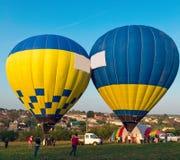 Mongolfiera sopra il campo con cielo blu Fotografie Stock