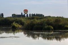 Mongolfiera variopinta nel cielo sopra vegetazione vicino alla torre di chiesa italiana Fotografia Stock