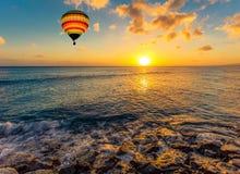 Mongolfiera variopinta sopra il mare al tramonto Fotografia Stock Libera da Diritti