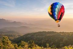 Mongolfiera variopinta sopra l'alta montagna al tramonto Immagine Stock Libera da Diritti