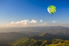 Mongolfiera verde sopra la montagna al tramonto Fotografia Stock Libera da Diritti