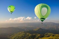 Mongolfiera verde sopra la montagna al tramonto Immagini Stock