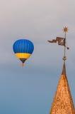 Mongolfiere blu e gialle in volo vicino Immagine Stock