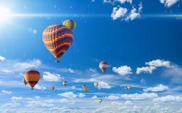 Mongolfiere variopinte che volano in cielo blu con le nuvole bianche Immagine Stock Libera da Diritti