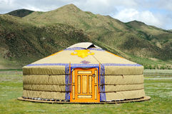 Mongolia yurt. With mountains, green gras, blue sky with clouds on a sunny day Royalty Free Stock Image