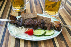 Mongolian Barbecue Beef Skewer with Beers. Traditional Mongolian barbecue at a modern restaurant with cucumbers and onions and tomatoes and wheat bread, with Stock Photo