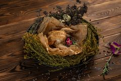 Mongolian chicken with herbs and spices in a nest of grass stock images