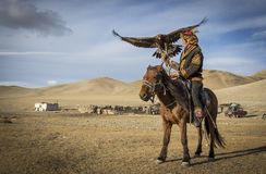 Mongolian eagle hunter with his eagle and horse Stock Photos