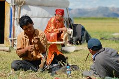 Mongolian family members fix traditional horse saddle and do housework in front of the yurt nomadic tent circa Kharkhorin, Mongo. KHARKHORIN, MONGOLIA - AUGUST Stock Photo