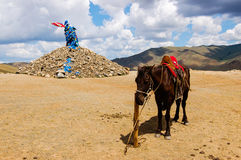 Mongolian horse and stone cairn. (ovoo), spiritual sites for worshiping the mountains, sky and revered sky deity. Travelers walk clockwise three times Stock Photo