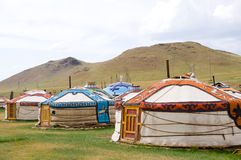 Mongolian jurts camp. Several mongolian coloured jurts encamped by hills stock photo