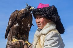 Mongolian Kazakh Eagle Hunter traditional clothing, holding a golden eagle on his arm Royalty Free Stock Photo