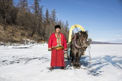 Mongolian man with his horse sledge on frozen lake Khovsgol. Mongolian man with his horse and a sledge on frozen lake Khovsgol in northern Mongolia Royalty Free Stock Photography