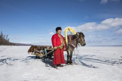 Mongolian man with his horse sledge on frozen lake Khovsgol. Mongolian man with his horse and a sledge on frozen lake Khovsgol in northern Mongolia Stock Photo