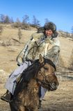 Mongolian man wearing a wolf skin jacket, riding his horse in a. Steppe in Northern Mongolia Royalty Free Stock Images
