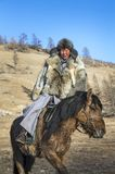 Mongolian man wearing a wolf skin jacket, riding his horse in a. Steppe in Northern Mongolia Royalty Free Stock Photography