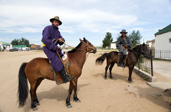 Mongolian Men on Horseback. A couple Mongolian men ride through a dirt road town in central Mongolia Stock Images