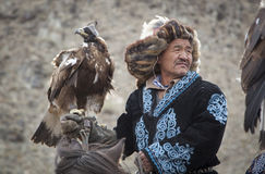 Mongolian nomad eagle hunter with his eagle. Bayan Ulgii, Mongolia, October 2nd, 2015: Old eagle hunter with his Altai Golden Eagle Royalty Free Stock Images